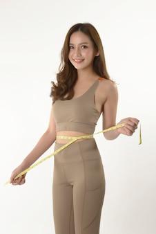 Slim asiática jovem medindo seu corpo