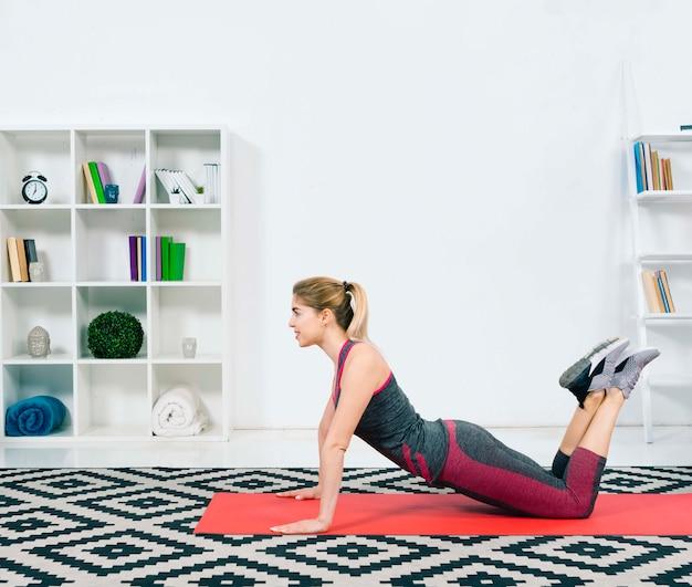 Slim fit jovem fazendo exercício no tapete de exercícios vermelho