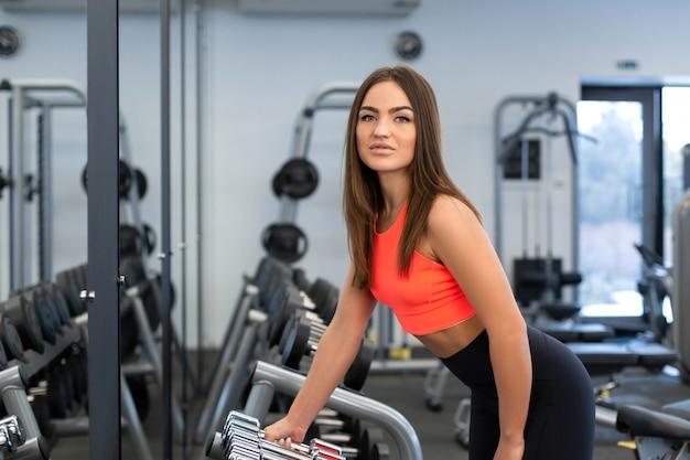 Slim fit mulher bonita leva halteres de uma linha no ginásio