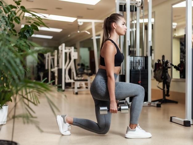 Slim fit mulher sportswear lunges com pernas com halteres nas mãos no ginásio. conceito de estilo de vida saudável