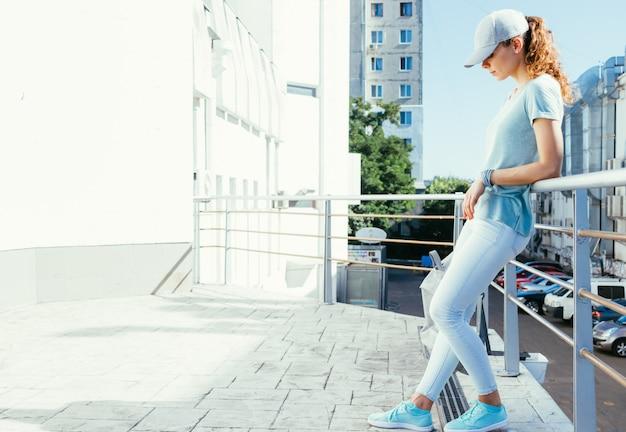 Slim garota em um boné e uma t-shirt com uma mochila nas mãos de pé sobre um telhado plano na cidade no verão