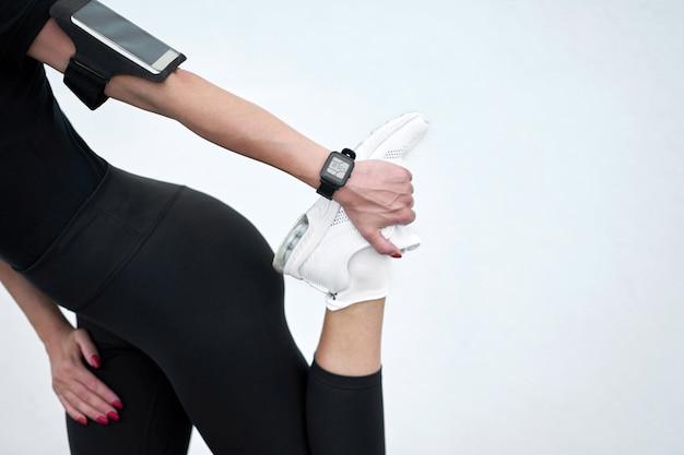 Slim garota vestindo sportswear preto, estendendo-se sobre fundo de parede branca