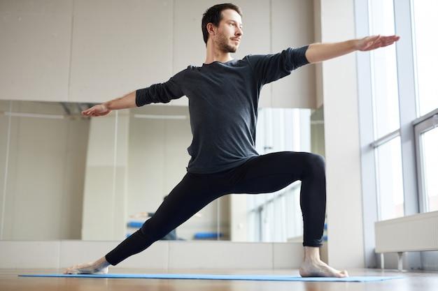 Slim homem fazendo pose de ioga em pé