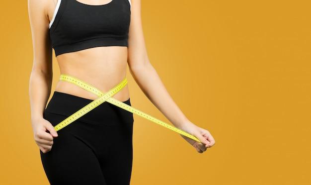 Slim jovem medindo a cintura dela