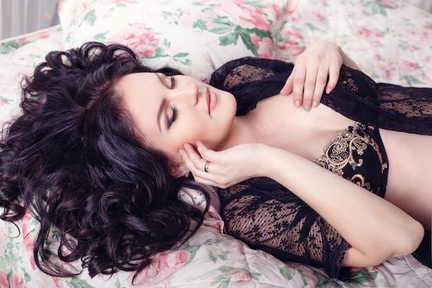 Slim linda mulher grávida sentada na cama no quarto. bela lingerie. gravidez elegante e sexy.