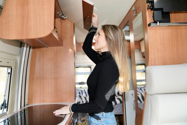 Slim linda mulher vivendo no estilo de vida interior de campista van motor rv casa em vanlife