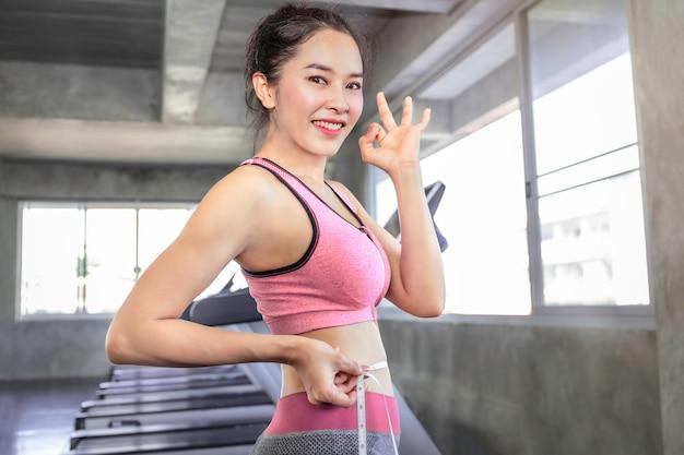 Slim mulher asiática no sportswear segurando a fita métrica em torno dela wais no ginásio de fitness.