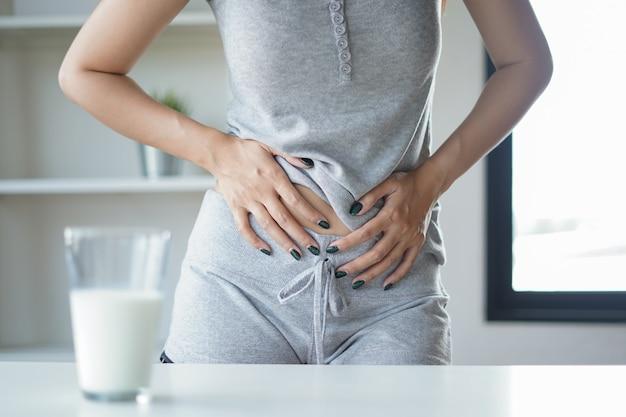 Slim mulher com dor de estômago e dor, segurando um copo de leite.
