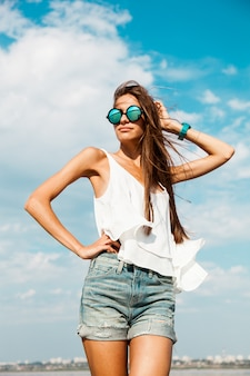 Slim mulher de camiseta branca posando perto da praia.