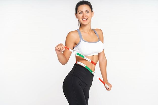 Slim mulher e fita métrica em torno de seu corpo