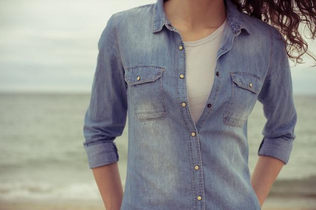 Slim mulher em uma camisa jeans e camiseta branca fica na praia contra o mar