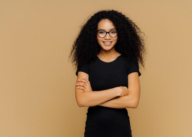 Slim mulher satisfeita com corte de cabelo afro, veste roupas casuais pretas, óculos ópticos, tem expressão confiante