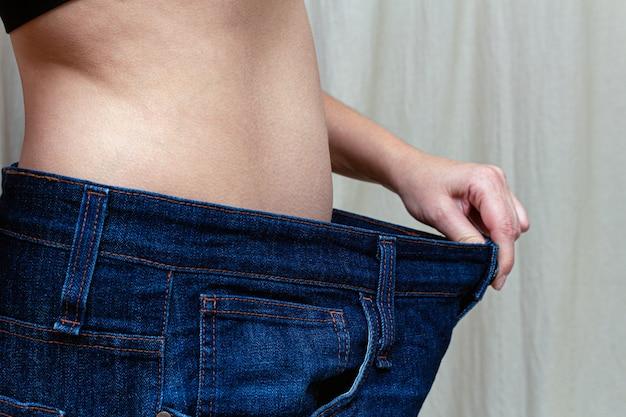 Slim mulher segurando jeans muito grandes. após uma dieta de perda de peso.