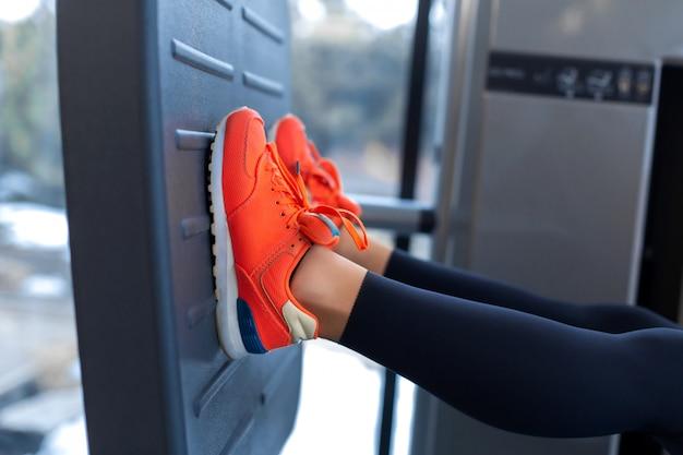 Slim mulher sorridente usando uma máquina de prensa de pernas e colocando as pernas na plataforma