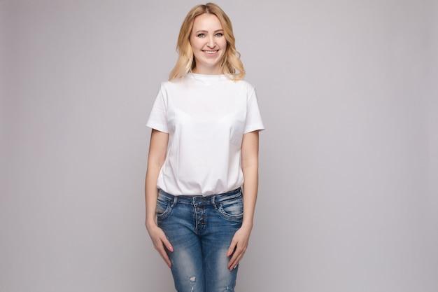 Slim mulher vestindo camisa branca e calça jeans permanente
