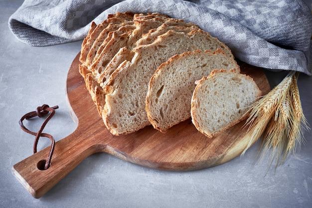 Slliced pão redondo branco com espigas de trigo na tábua de madeira em cinza
