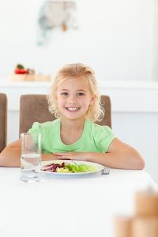 Smart girl sentada em uma mesa para comer sua salada saudável