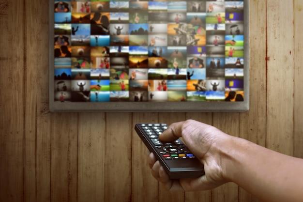 Smart tv e mão pressionando o controle remoto