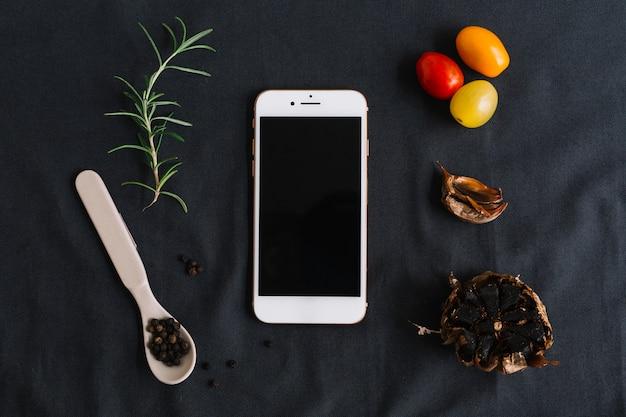 Smartphone; alecrim; tomate cereja; pimenta preta e alho em fundo escuro