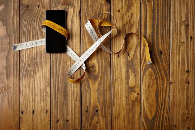 Smartphone amarrado em medidor de alfaiataria apresentado em vista de mesa de madeira rústica