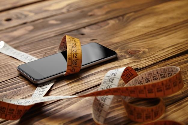 Smartphone amarrado em medidor de alfaiataria apresentado em vista de perto de mesa de madeira rústica