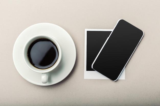 Smartphone ao lado do café na mesa de madeira.