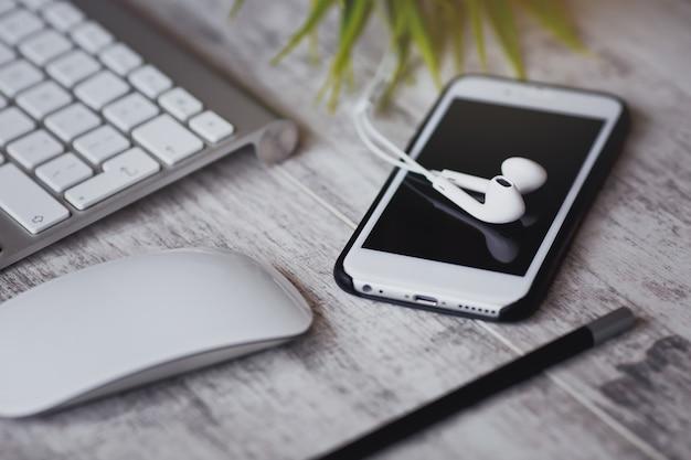 Smartphone branco com fones de ouvido e teclado na mesa