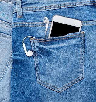 Smartphone branco com fones de ouvido no bolso de trás da calça jeans azul