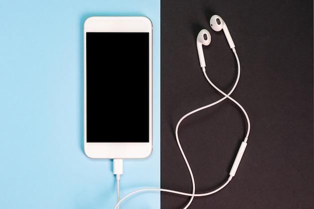 Smartphone branco com fones de ouvido. vista do topo