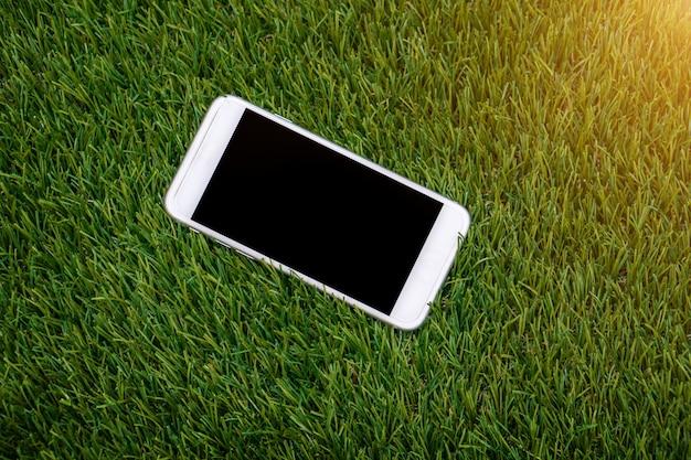 Smartphone branco com tela isolada na grama falsa