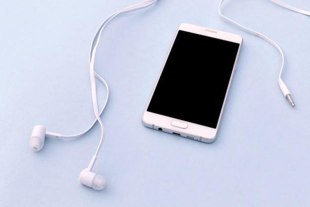 Smartphone branco e fones de ouvido brancos no fundo azul.