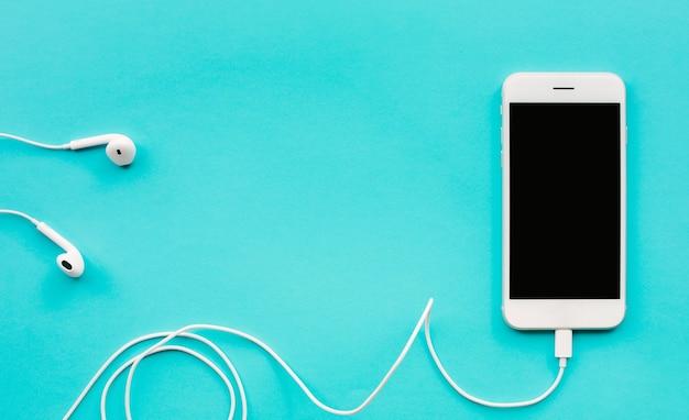 Smartphone branco, móvel sobre fundo de cor azul.