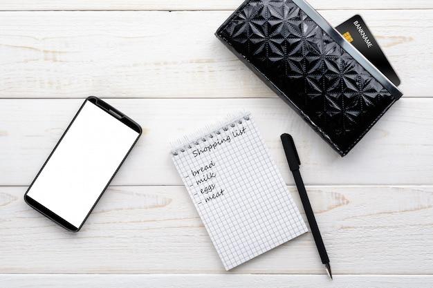 Smartphone, caderno, caneta e cartão de crédito em uma mesa branca