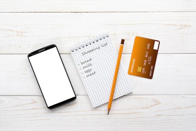 Smartphone, caderno, lápis e cartão de crédito em uma mesa branca