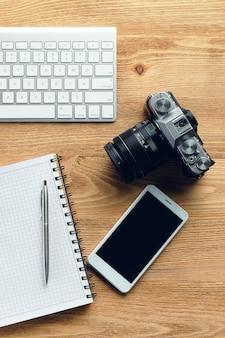 Smartphone, caneta e bloco de notas, câmera e teclado no escritório de turismo