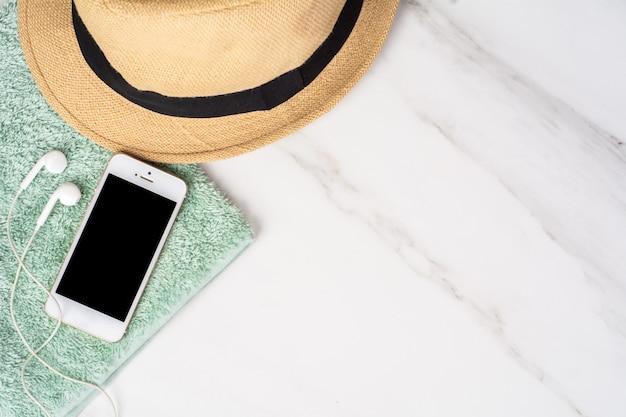 Smartphone, chapéu, protetor solar e toalha.