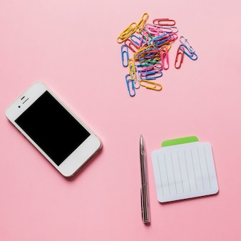 Smartphone; clipes de papel coloridos com caneta e bloco de notas no fundo rosa