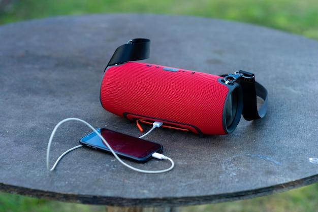 Smartphone com alto-falantes portáteis é colocado sobre uma mesa de madeira.