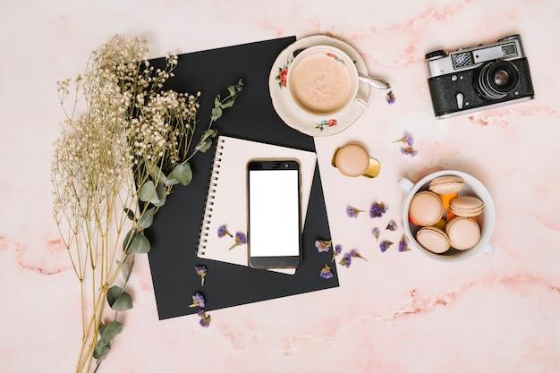 Smartphone com biscoitos, câmera e xícara de café na mesa