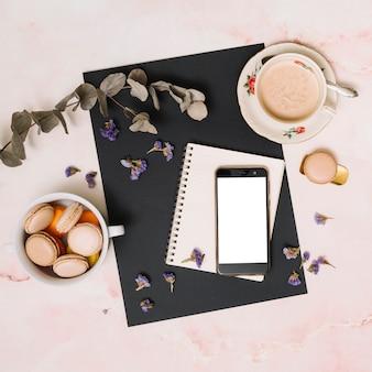 Smartphone com biscoitos e xícara de café na mesa