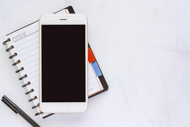 Smartphone com caderno espiral e caneta preta sobre fundo de mármore