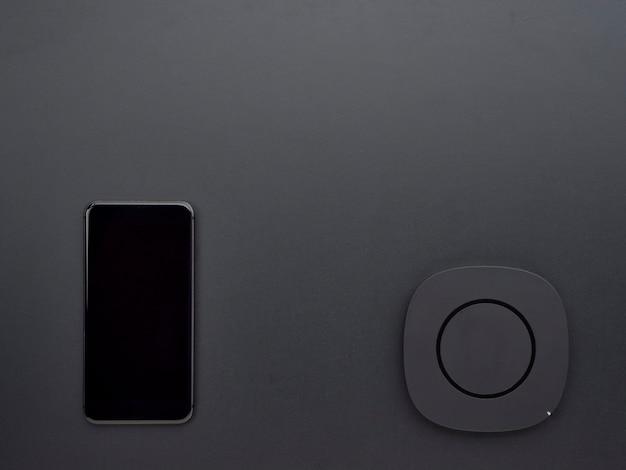 Smartphone com carregador sem fio preto.