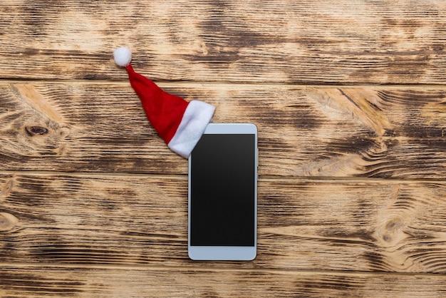 Smartphone com chapéu de papai noel na mesa de madeira
