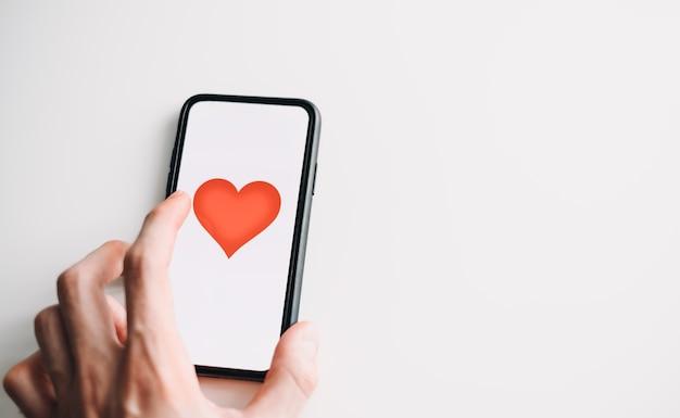 Smartphone com coração vermelho na tela