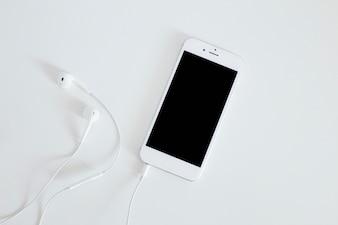 Smartphone com fone de ouvido isolado no fundo branco