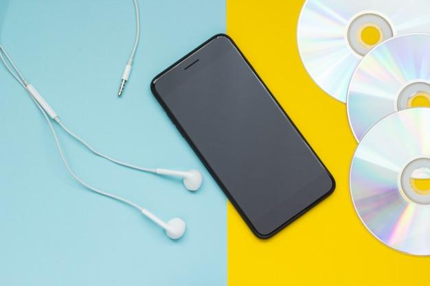 Smartphone com fones de ouvido e cds em um fundo amarelo azul