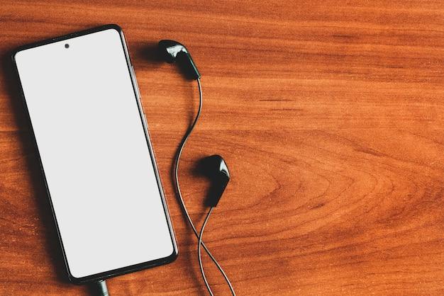 Smartphone com fones de ouvido e tela em branco