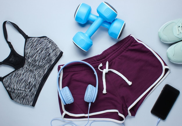 Smartphone com fones de ouvido, halteres de plástico, sutiã esportivo, shorts, tênis em fundo cinza