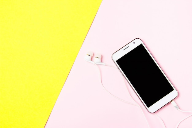 Smartphone com fones de ouvido na arte amarelo e rosa fundo