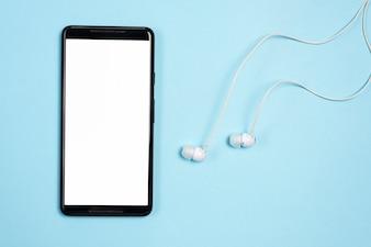 Smartphone com fones de ouvido no fundo azul
